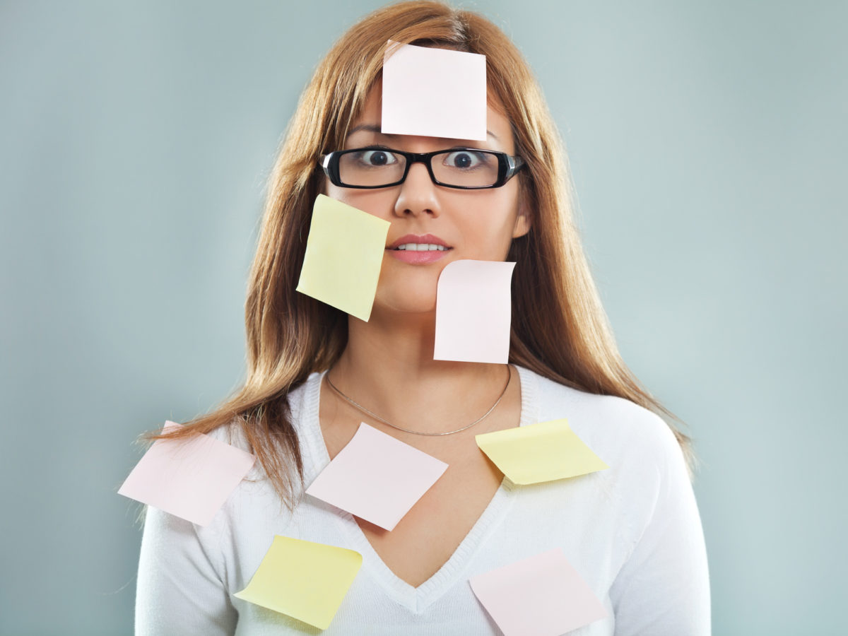 Beautiful young woman covered with post it notes